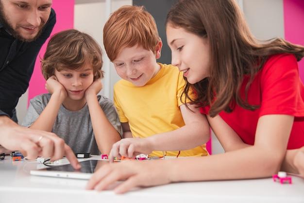Groep positieve attente kinderen met leraar verzamelen rond tafel met tablet en elektronische details en studieproject bespreken tijdens les robotica op school Premium Foto