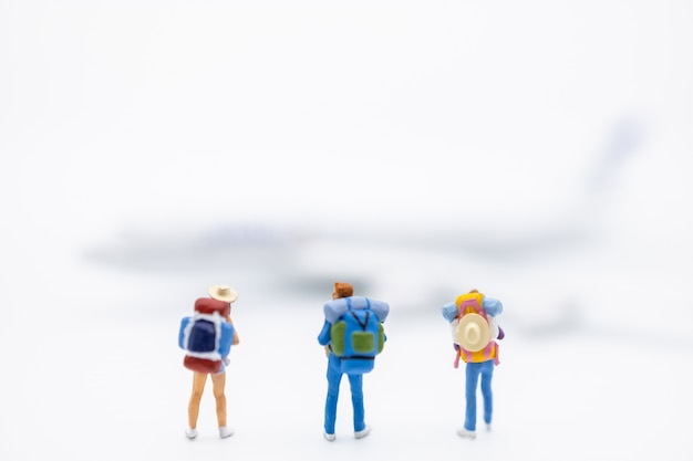 Groep reizigers miniatuurcijfer met rugzak die zich op wit met ministuk speelgoed vliegtuig bevinden. Premium Foto