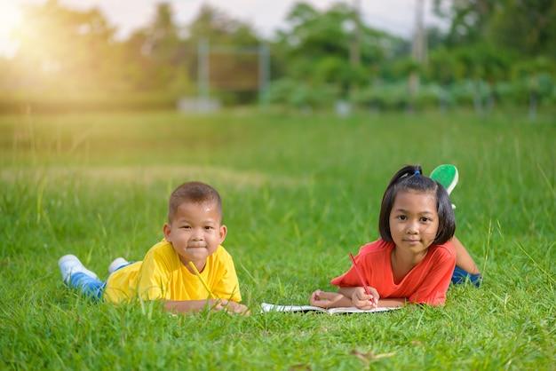 Groep schoolkinderen die in openlucht gelukkig kijken kleuren Premium Foto