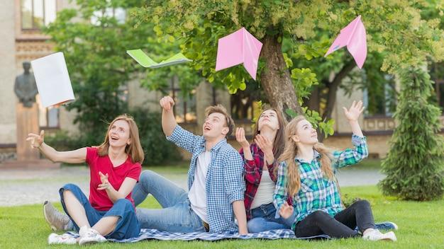 Groep studenten die boeken in de lucht werpen Gratis Foto