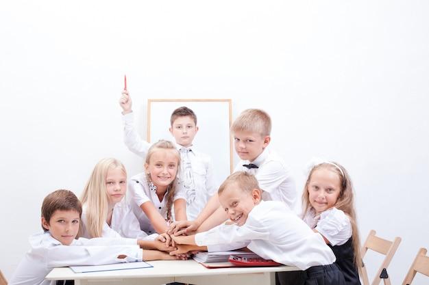 Groep tiener leerlingen. ze houden hun handen bij elkaar Gratis Foto