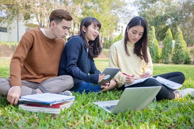 Groep universitaire studenten aziatische zittend op het groene gras werken en lezen buiten samen in een park Premium Foto