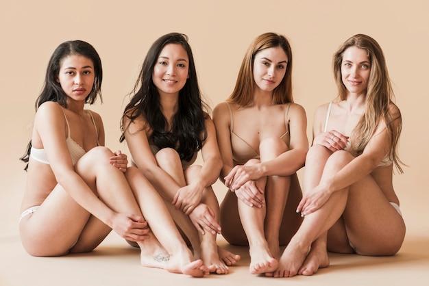 Groep van aantrekkelijke jonge vrouwen in ondergoed zitten in de studio Gratis Foto