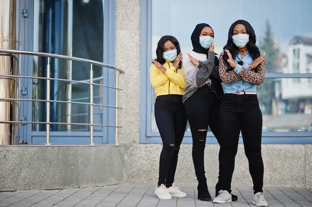 Groep van drie afro-amerikaanse jonge vrijwilligers dragen gezichtsmasker buitenshuis. coronavirus-quarantaine en wereldwijde pandemie. Premium Foto