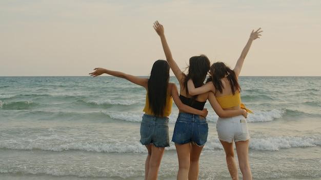 Groep van drie aziatische jonge vrouwen die op strand lopen Gratis Foto