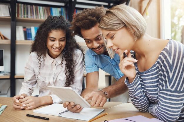 Groep van drie jonge knappe starters die in lichte coworkingruimte zitten, die over toekomstig project spreken, door ontwerpvoorbeelden op digitale tablet kijken. vrienden glimlachen, praten over werk. Gratis Foto