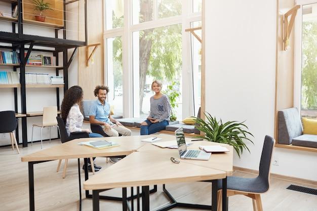 Groep van drie jonge multi-etnische startups die samenwerken in coworking-ruimte, met pauze van brainstormen. jonge mensen lachen, praten, plezier hebben Gratis Foto