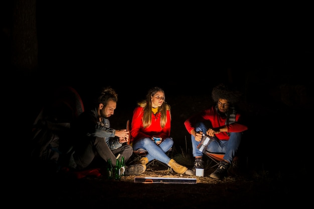 Groep van drie vrienden kamperen in het bos met led-licht 's nachts Gratis Foto