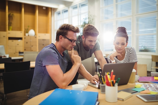 Groep van grafisch ontwerpers bespreken over laptop op hun bureau Gratis Foto
