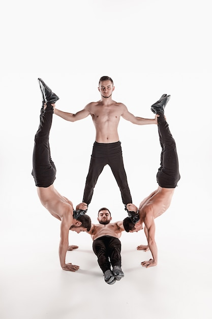 Groep van gymnastiek acrobatische blanke mannen per saldo poseren Gratis Foto