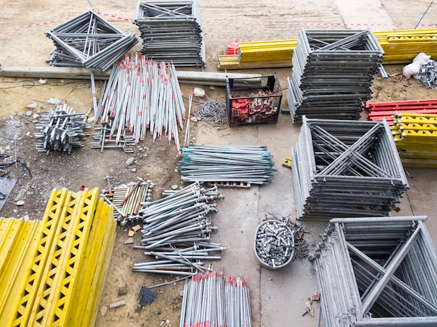Groep van het metalen frame en de uitrustingsstapel op het betonnen grondblad voor gebruik om de constructie te bouwen Premium Foto