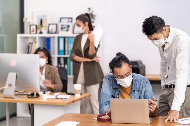 Groep van interraciale bedrijfsmedewerkers draagt een beschermend gezichtsmasker in een nieuw normaal kantoor Premium Foto