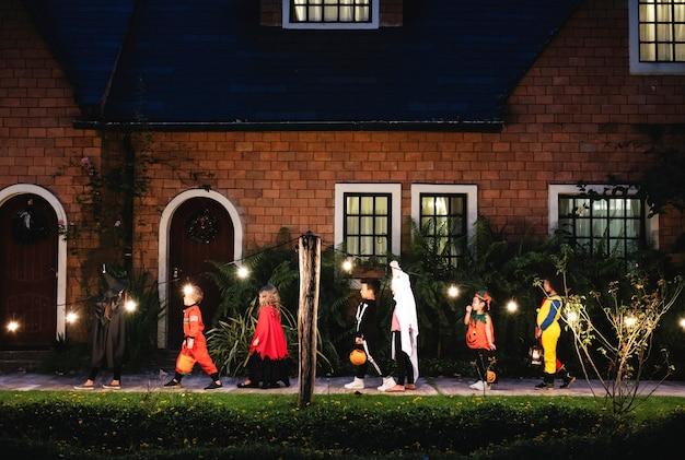 Groep van kinderen met halloween-kostuums lopen om te trick or treat Gratis Foto