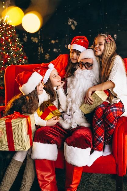 Groep van kinderen zitten met santa en presenteert op kerstavond Gratis Foto