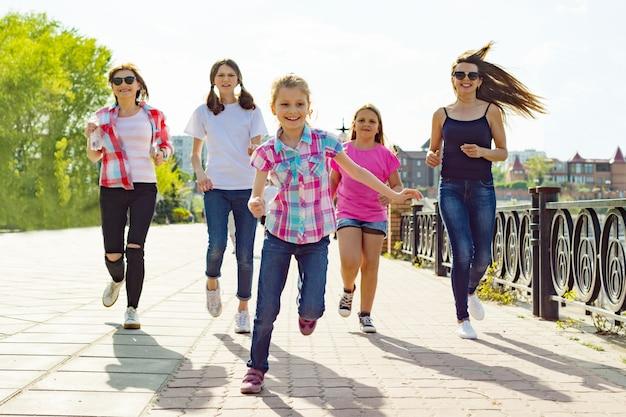 Groep van moeders en dochters lopen langs de weg in het park Premium Foto