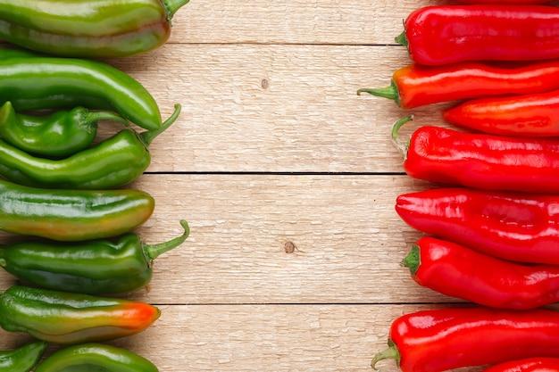 Groep van rode en groene paprika's op oude houten tafel Premium Foto