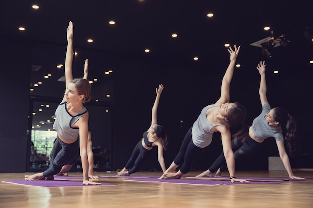Groep van sportieve mix race van blanke en aziatische mensen, zowel vrouwen als mannen, beoefenen van yoga pose bij studio gym, yoga en fitness werken gezondheidszorg concept Premium Foto