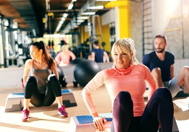 Groep van toegewijde mensen doen oefeningen op stepper in gym. op de achtergrond hun spiegelbeeld. Premium Foto