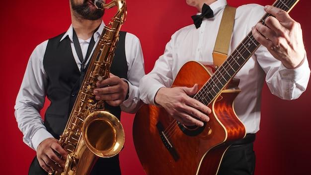 Groep van twee muzikanten, mannelijke jazzband, gitarist en saxofonist in klassieke kostuums improviseren op muziekinstrumenten in een studio op rode achtergrond Premium Foto