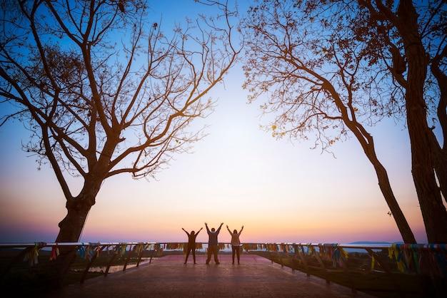 Groep van vier mensen staat op de top van berg in winnaar pose. Premium Foto