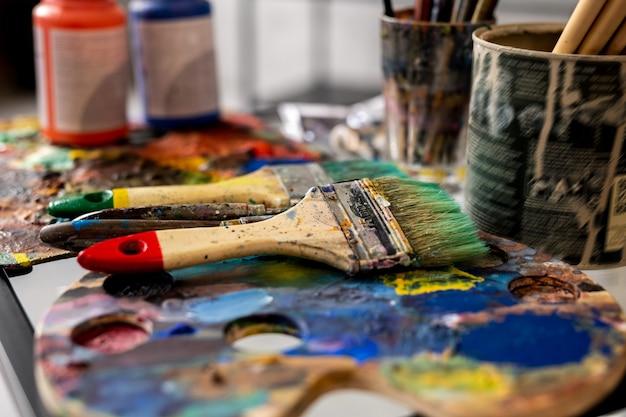 Groep verfborstels en paletten van gouachekruiken op de werkplaats van de moderne schilder Premium Foto