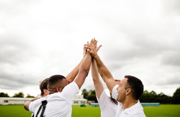 Groep voetballers die een hoogte vijf doen Premium Foto