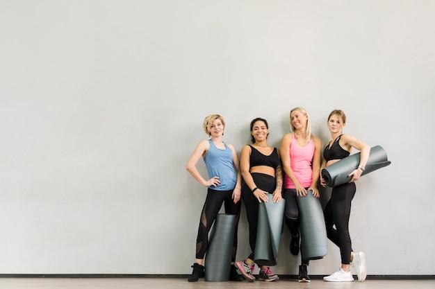 Groep volwassen vrouwen die bij de gymnastiek stellen Gratis Foto