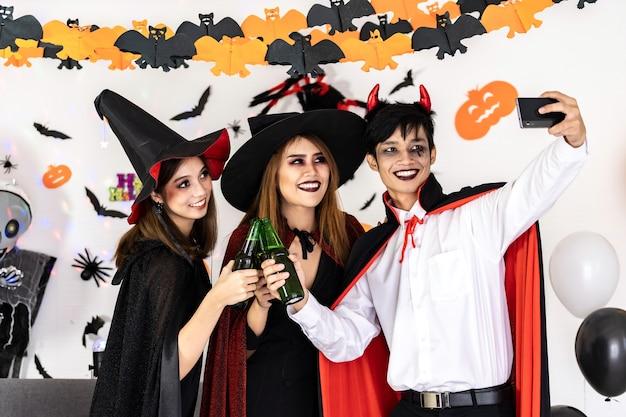 Groep vrienden aziatische jonge volwassen mensen vieren een halloween-feest. ze dragen halloween-kostuums en nemen selfie-foto's. halloween vieren en internationaal vakantieconcept. Premium Foto