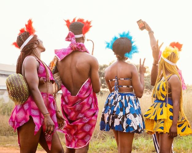 Groep vrienden bij afrikaans carnaval die kostuums dragen Gratis Foto