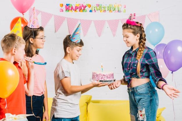 Groep vrienden die de verjaardag van het meisje met cake thuis vieren Gratis Foto