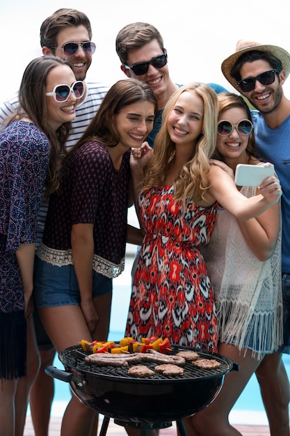 Groep vrienden die een selfie nemen dichtbij pool Premium Foto