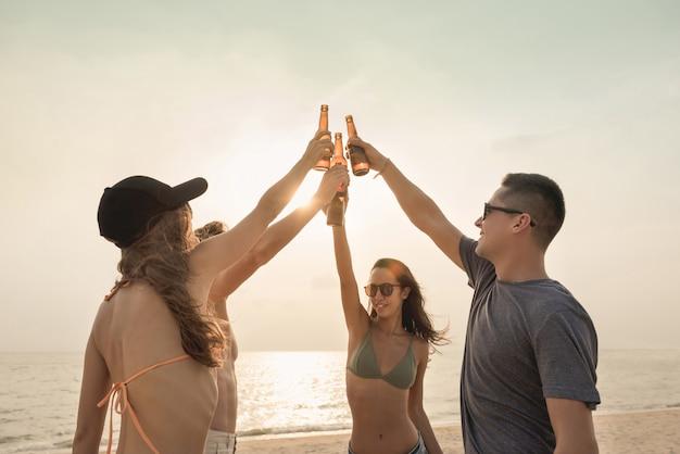 Groep vrienden die en bij het strand in schemering vieren drinken Premium Foto