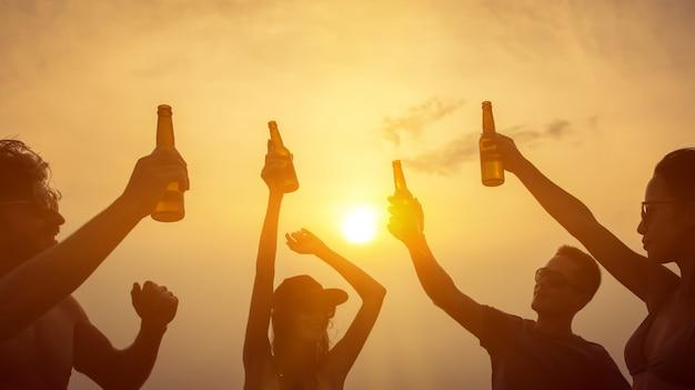 Groep vrienden die en bij het strand in schemeringzonsondergang vieren drinken Premium Foto