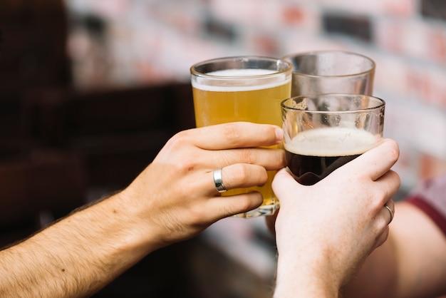 Groep vrienden die glas alcoholische dranken roosteren Gratis Foto