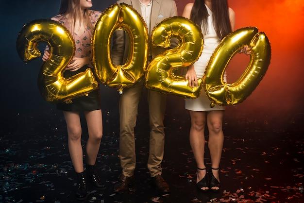 Groep vrienden die gouden ballons houden bij partij Gratis Foto