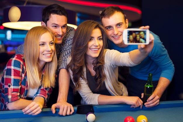 Groep vrienden die herinneringen van biljartclub vangen Gratis Foto