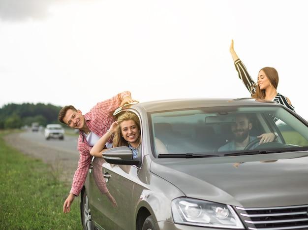Groep vrienden die in de auto reizen die uit door open venster hangen Gratis Foto