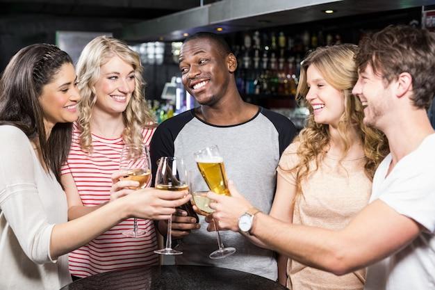 Groep vrienden die met bier en wijn roosteren Premium Foto