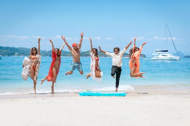 Groep vrienden die op een strand springen Premium Foto