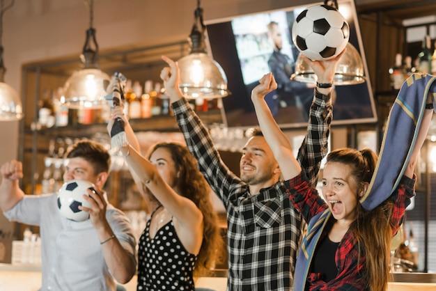 Groep vrienden die op sport letten samen vierend overwinning in de bar Gratis Foto