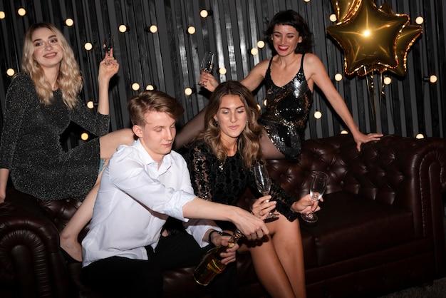 Groep vrienden die oudejaarsavond thuis vieren Gratis Foto
