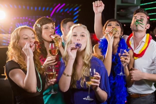 Groep vrienden die partijhoorn in bar blazen Premium Foto