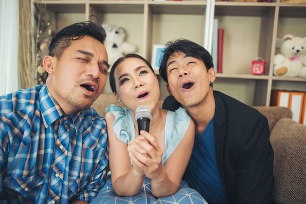 Groep vrienden die pret hebben bij woonkamer die een lied samen zingen Gratis Foto