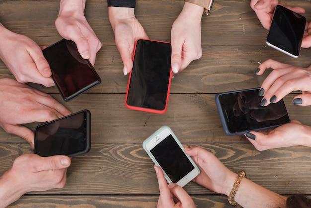 Groep vrienden die smartphones gebruiken Gratis Foto