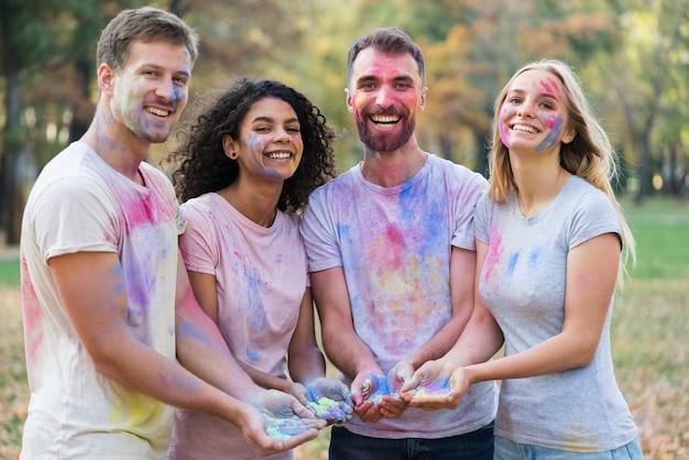 Groep vrienden die terwijl het houden van verf stellen Gratis Foto