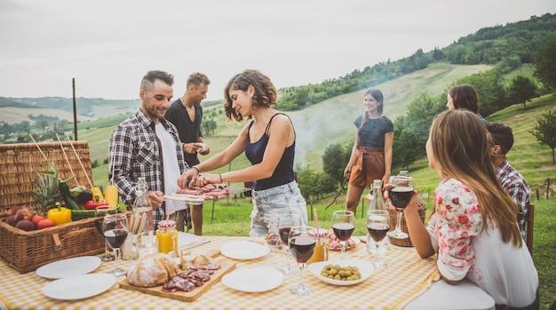 Groep vrienden die tijd doorbrengen met het maken van een picknick en een barbecue Premium Foto
