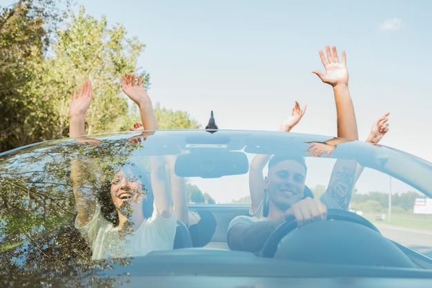 Groep vrienden die wapens in auto opheffen Gratis Foto
