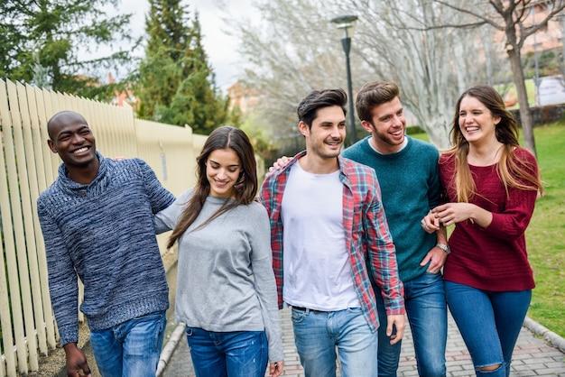 Groep vrienden lopen en praten Gratis Foto