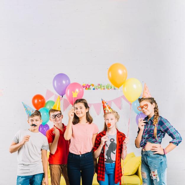 Groep vrienden met ballonnen en rekwisieten Gratis Foto