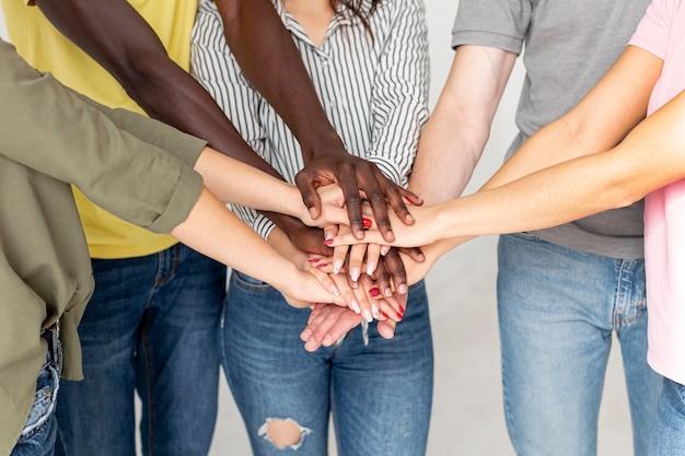 Groep vrienden met handen op elkaar Gratis Foto